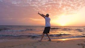 Den idrotts- mannen som öva Tai Chi asiatiska kampsporter på havet, sätter på land i morgonen stock video