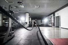 Den idrotts- mannen som gör någon kors-utbildning, övar med ett rep i idrottshall Crossfit Royaltyfri Fotografi