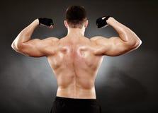 Den idrotts- mannen som gör bodybuilding, flyttar sig för de tillbaka musklerna Arkivbilder