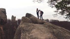 Den idrotts- pojken och flickan med en turist vandrar att klättra det steniga berget, då att få på överkanten som rymmer deras hä stock video
