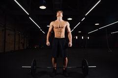 Den idrotts- pumpade mankroppsbyggaren står framme av stång i idrottshall Konditionman som är klar att arbeta royaltyfria foton