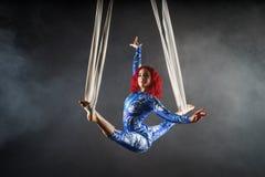 Den idrotts- sexiga flyg- cirkuskonstnären med rödhåriga mannen i blått kostymerar dans i luften med jämvikt arkivfoto