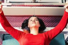 Den idrotts- unga flickan lyfter skivstången på simulatorn i idrottshallen sporttyngdlyftning arkivbilder