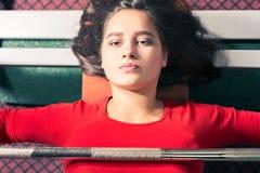 Den idrotts- unga flickan lyfter skivstången på simulatorn i idrottshallen sporttyngdlyftning royaltyfria foton