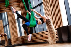 Den idrotts- unga flickan med iklätt långt blont hår sportkläderna gör kondition på det gröna flyg- silket i arkivbild