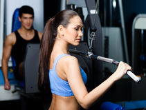 Den idrotts- unga kvinnan fungerar ut på konditionidrottshallutrustning Arkivbilder