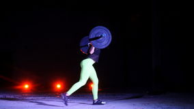 Den idrotts- unga kvinnan som gör olik styrka, övar med en skivstång, utfall, squats På natten i ljus av lager videofilmer