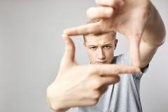 Den iklädda blonda grabben en vit t-skjorta håller hans händer framme av honom som gör med fingrar en form av en ram på viten arkivbilder