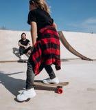 Den iklädda fadern och hans lilla son den tillfälliga kläderna rider skateboarder och har gyckel i en skridsko parkerar med glidb arkivbilder