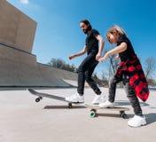 Den iklädda fadern och hans lilla son den tillfälliga kläderna rider skateboarder i en skridsko parkerar med glidbanor på den sol arkivbilder