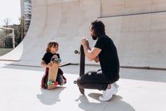 Den iklädda fadern och hans son den tillfälliga kläderna placerar bredvid skateboarderna i en skridsko parkerar på den soliga dag royaltyfria bilder