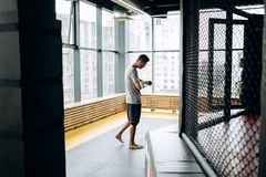 Den iklädda grabben den gråa t-skjortan slår in en hand förbinder på hans hand i den boxas idrottshallen mot bakgrunden av panora fotografering för bildbyråer