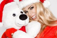 Den iklädda härliga sexiga blonda kvinnliga modellen en Santa Claus hatt omfamnar en vit nallebjörn i ett rött lock Christm Arkivfoto