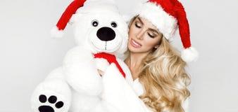 Den iklädda härliga sexiga blonda kvinnliga modellen en Santa Claus hatt omfamnar en vit nallebjörn i ett rött lock Christm Royaltyfri Bild