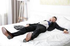 Den iklädda mannen för affärsdräkten avverkar sovande fotografering för bildbyråer
