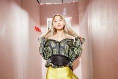 Den ikl?dda modeung flickabloggeren ett stilfullt svart och gult omslag och gula kortslutningar poserar i en provhytt av arkivbilder