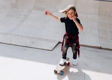 Den iklädda pojken den tillfälliga kläderna rider skateboarden i en skridsko parkerar på den soliga varma dagen royaltyfria bilder