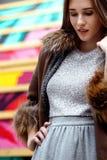 Den iklädda trendiga långhåriga flickan en grå klänning och ett långt brunt fårskinnlag poserar i gatan fotografering för bildbyråer