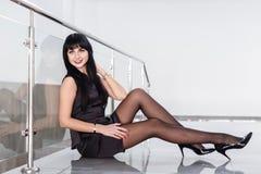 Den iklädda unga attraktiva allvarliga kvinnan en svart affärsdräkt med en kort kjol sitter på golvet i ett vitt kontor royaltyfri bild