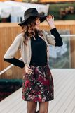 Den ikl?dda stilfulla flickan en svart halvpolokrage, en beige udde, en stilfull kort kjol och en svart hatt med breda klockor po arkivfoton