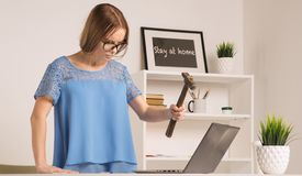 Den ilskna affärskvinnan gick tokig med hammaren och bärbara datorn royaltyfria foton