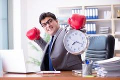 Den ilskna affärsmannen med boxninghandskar i begrepp för tidledning arkivbilder