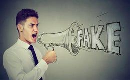 Den ilskna affärsmannen som skriker i en megafonfördelning, fejkar nyheterna arkivfoto