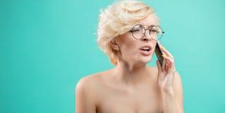 Den ilskna attraktiva blonda kvinnan ropar, medan tala på telefonen royaltyfri fotografi