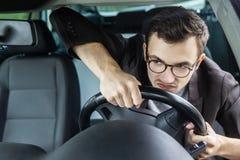 Den ilskna chauffören ser till och med windsheelden Han kör hans bil och rymmer styrninghjulet med båda händer fotografering för bildbyråer
