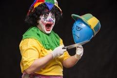 Den ilskna fula clownen önskar att döda en ballong i locket Royaltyfri Bild