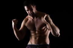 Den ilskna idrotts- mannen i attack poserar på black fotografering för bildbyråer