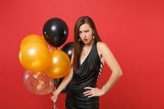 Den ilskna irriterade kvinnan i den svarta klänningen som rymmer luftballonger som står, i att hota, poserar, medan att fira som  royaltyfri bild