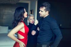 Den ilskna kvinnan hotar den illojala mannen som flörtar flickan i röd klänning Arkivfoto