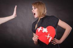 Den ilskna kvinnan rymmer bruten hjärta som skriker på mannen arkivbild