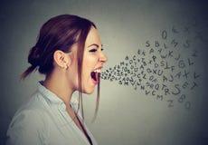 Den ilskna kvinnan som skriker med alfabet, märker flyg ut ur mun royaltyfria bilder