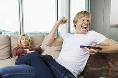 Den ilskna kvinnan som stirrar på den gladlynta mannen som håller ögonen på han, TV i vardagsrum hemma Royaltyfri Foto