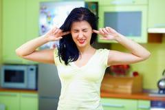 Den ilskna kvinnan stänger öron med fingrar, hemmiljö royaltyfri foto