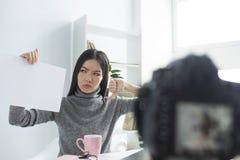 Den ilskna kvinnliga bloggeren sitter på tabellen och antecknar videoen Hon ser till papperet som hon rymmer Flickan är royaltyfria bilder