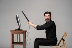 Den ilskna mannen förstör ett tangentbord royaltyfri bild