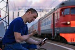 Den ilskna mannen hotar med hans näve i smartphonen på stationen nära drevet royaltyfri foto