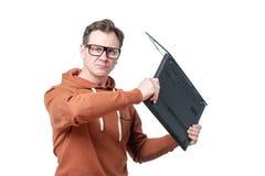 Den ilskna mannen i exponeringsglas och gul tröja svänger en bärbar dator som isoleras på vit bakgrund royaltyfria foton