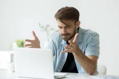 Den ilskna mannen ogillar med fejkar online-nyheterna som ser bärbara datorn Arkivfoton