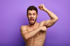 Den ilskna mannen ropar under depilation royaltyfri foto