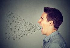 Den ilskna mannen som skriker med alfabet, märker flyg ut ur öppen mun royaltyfri fotografi