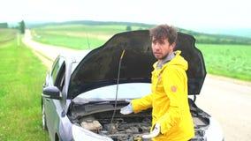 Den ilskna mannen svär och försöket att fixa en bruten bil stock video