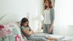 Den ilskna modern argumenterar gräla på henne för att förarga den lilla dottern som hemma ligger på säng i ljust sovrum arkivfilmer