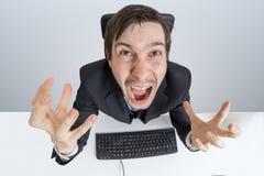Den ilskna och frustrerade mannen arbetar med datoren och att ropa Arkivbild