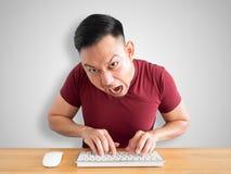 Den ilskna och rasande mannen arbetar med datoren arkivbilder