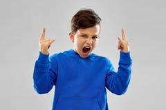 Den ilskna pojken i blå hoodievisning vaggar gest royaltyfri bild