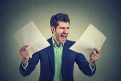 Den ilskna skrikiga affärsmannen med dokument skyler över brister skrivbordsarbete Arkivfoton